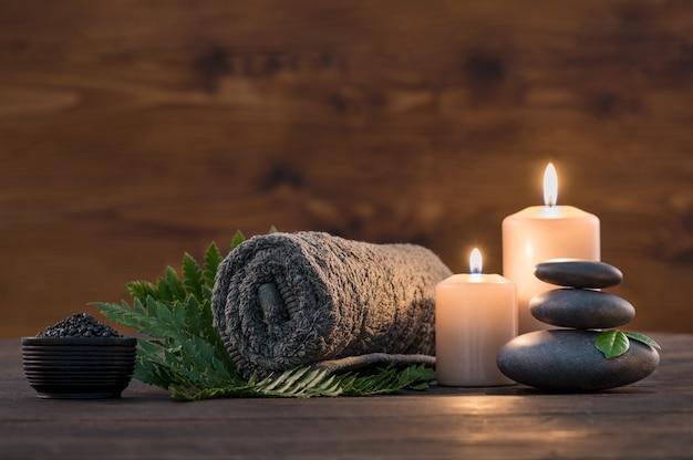Brązowy ręcznik ze świecami i czarny gorący kamień na podłoże drewniane.