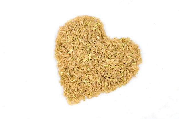Brązowy ryż ułożone w kształcie serca na białym tle.