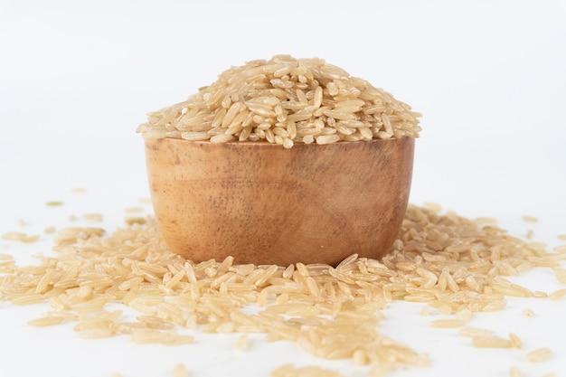 Brązowy ryż w drewnianej misce przelewający się i rozsypany na podłodze.