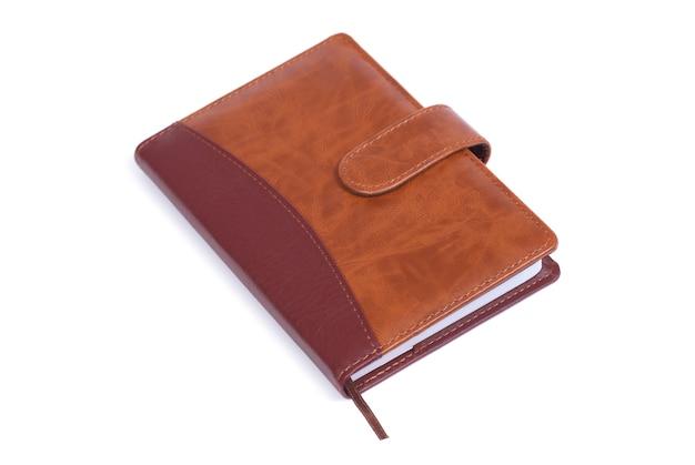 Brązowy skórzany notebook na białym tle na białej powierzchni
