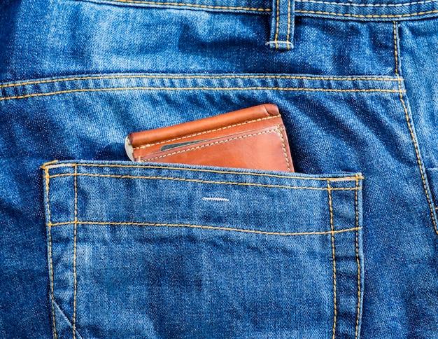 Brązowy skórzany portfel w niebieskiej kieszeni z dżinsami