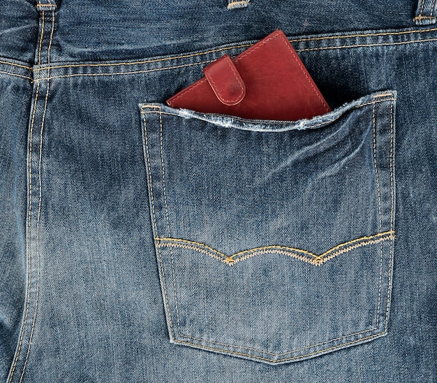 Brązowy skórzany portfel w tylnej kieszeni niebieskich dżinsów