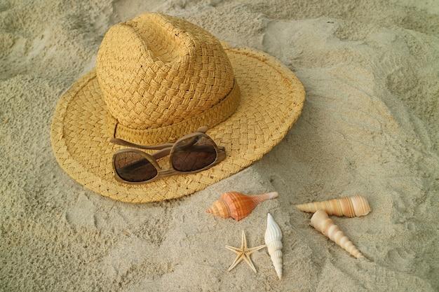 Brązowy słomkowy kapelusz i okulary przeciwsłoneczne na piaszczystej plaży z wieloma rodzajami muszelek