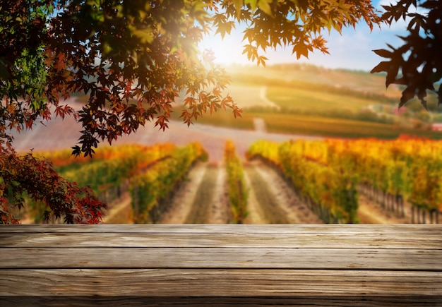 Brązowy stół z drewna w jesiennym krajobrazie winnicy z pustą przestrzenią na makietę produktu.