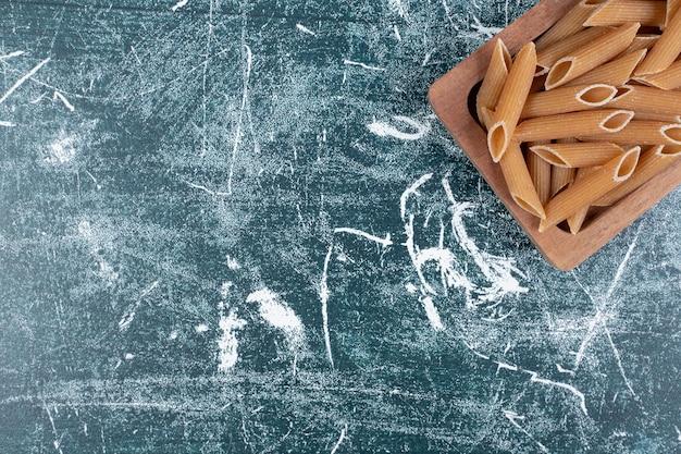 Brązowy surowy makaron penne na drewnianym talerzu.