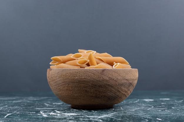 Brązowy surowy makaron penne w drewnianej misce.