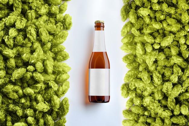 Brązowy szablon butelki piwa na białym tle z dwoma rzędami szyszek chmielowych. na szkle znajduje się szara etykieta. widok z góry. makieta gotowa na twoją wizytówkę.