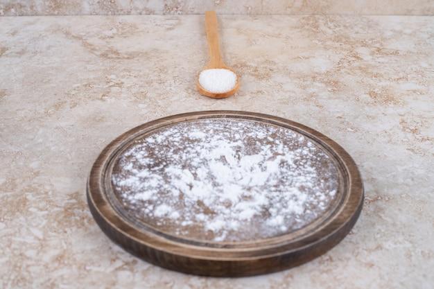 Brązowy talerz mąki i drewniana łyżka cukru