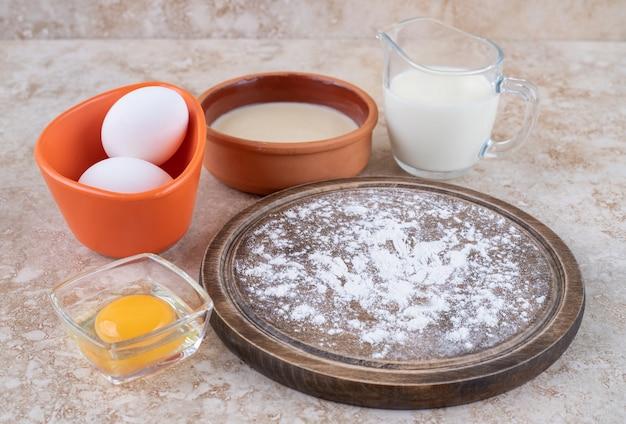 Brązowy talerz mąki i surowe jajka ze szklaną filiżanką mleka