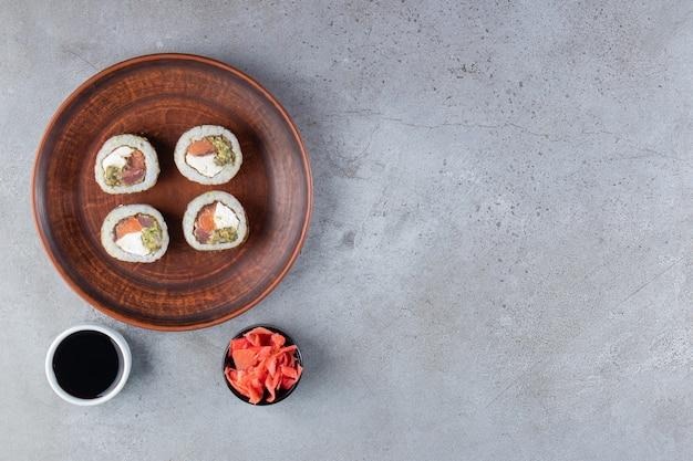Brązowy talerz rolek sushi ze świeżą rybą na kamiennym tle.