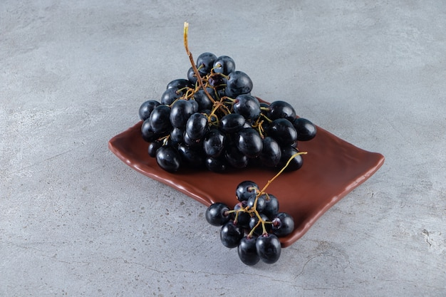Brązowy talerz świeżych czarnych winogron na kamiennym tle.