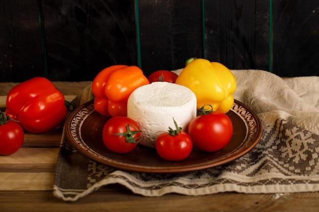 Brązowy talerz z serem whtie, pomidorem i papryką w środku
