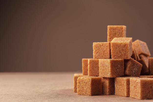 Brązowy trzciny cukrowej kostki na jasnobrązowym tle