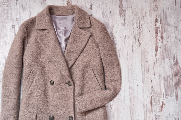 Brązowy wełniany płaszcz, drewniane tła