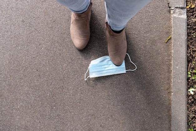 Brązowy zamszowy but kobiety za chwilę stąpnie po masce na chodniku.