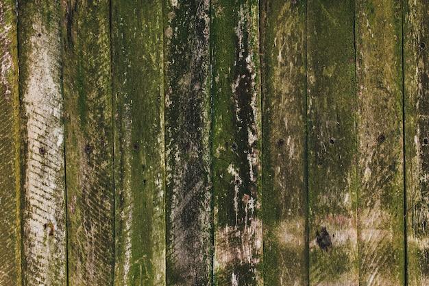 Brązowy zielony stary drewniany płot. stare deski tekstury