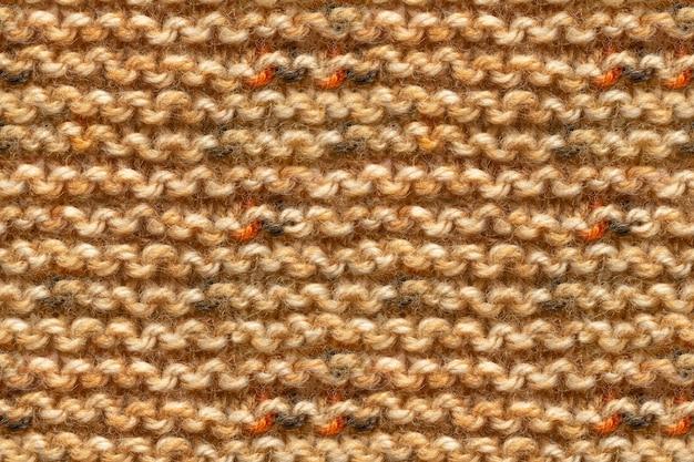 Brązowy żółty beżowy kolor dzianiny tekstura tkaniny. dziewiarska migawka makro tekstury. beżowa dzianina