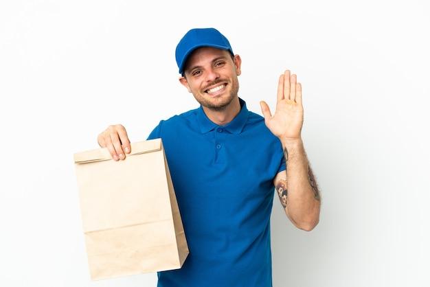 Brazylijczyk biorący torbę jedzenia na wynos na białym tle pozdrawiając ręką ze szczęśliwym wyrazem twarzy