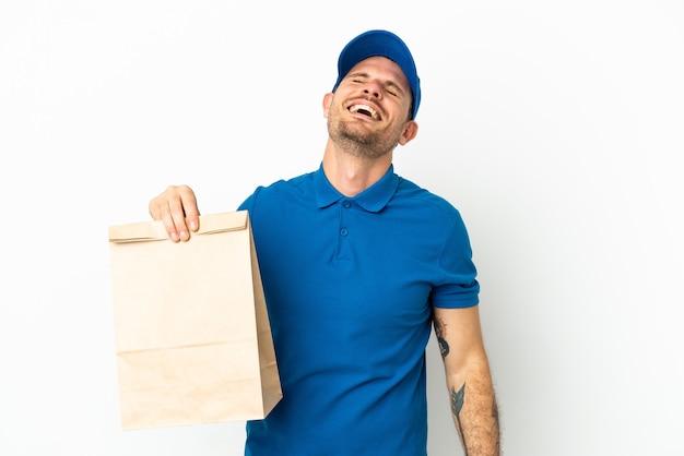 Brazylijczyk biorący torbę jedzenia na wynos na białym tle śmiejąc się