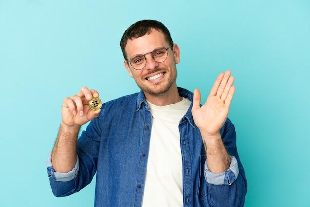 Brazylijczyk trzymający bitcoina nad odizolowanym niebieskim tłem