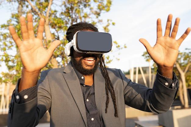 Brazylijczyk w biznesowym stroju i okularach wirtualnej rzeczywistości o zachodzie słońca