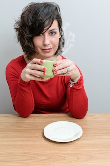 Brazylijka, z włosami zakrywającymi jedno oko, z filiżanką kawy i twarzą do kamery.