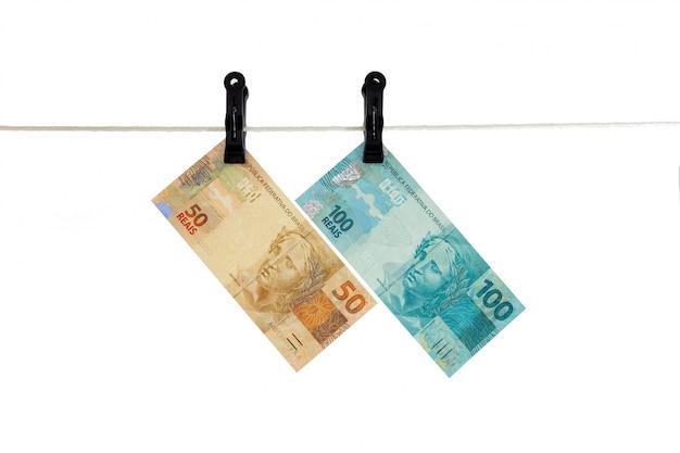 Brazylijscy istni banknoty w clothesline brudnym pieniądze pojęciu - odizolowywającym - pranie brudnych pieniędzy -