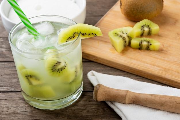 Brazylijska caipirinha kiwi w szklance z lodem z kawałkami owoców na desce