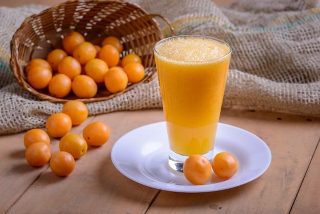 Brazylijska caja owocowa. szklanka soku na drewnianym stole.