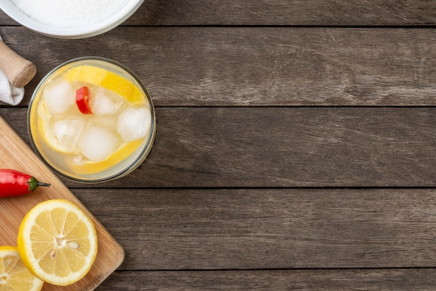 Brazylijska cytryna i czerwona chili caipirinha w szklance z lodem i plasterkami owoców na drewnianej desce z miejscem na kopię