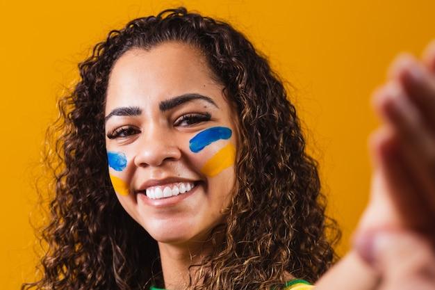 Brazylijska fanka z pomalowaną twarzą robi selfie