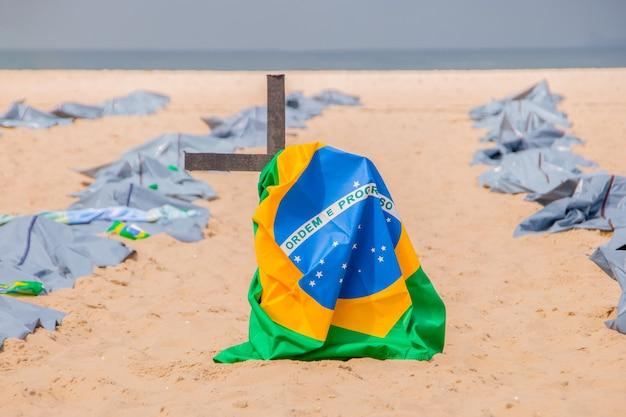 Brazylijska flaga na krzyżu podczas demonstracji przeciwko polityce rządów brazylijskich w sprawie koronawirusa na plaży copacabana w rio de janeiro