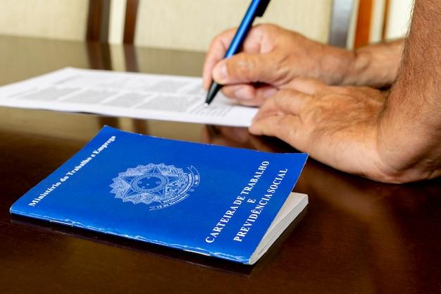 Brazylijska karta pracy, a w tle ręka podpisująca kontraktową koncepcję zatrudniania pracowników