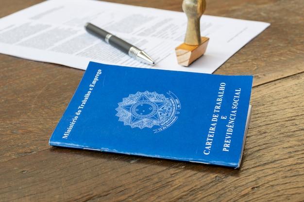 Brazylijska karta pracy z pieczątką, długopisem i papierem na rustykalnym stole. koncepcja umowy o pracę.