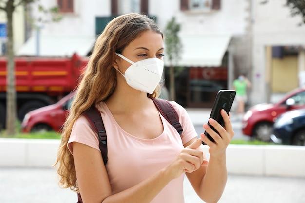 Brazylijska kobieta nosi maskę ochronną na twarzy z inteligentny telefon