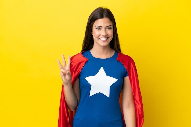 Brazylijska kobieta super hero na białym tle na żółtym tle szczęśliwa i licząca trzy palcami