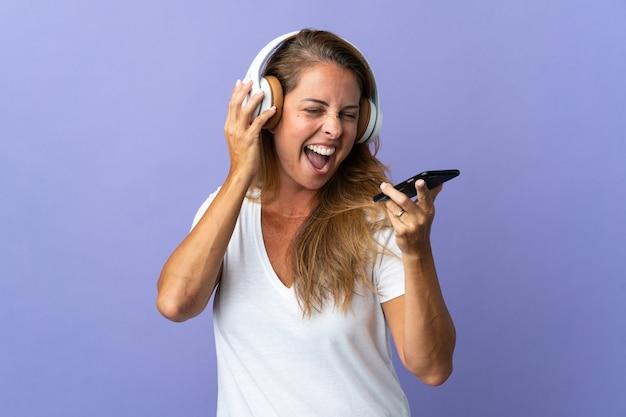 Brazylijska kobieta w średnim wieku na fioletowej ścianie słuchania muzyki z telefonu komórkowego i śpiewu