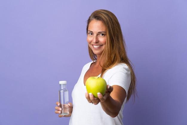 Brazylijska kobieta w średnim wieku na fioletowym z jabłkiem i butelką wody