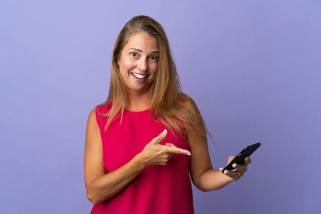 Brazylijska kobieta w średnim wieku samodzielnie na fioletowo przy użyciu telefonu komórkowego i wskazując go