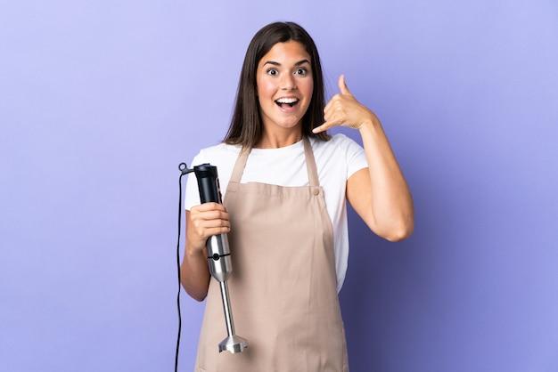 Brazylijska kobieta za pomocą ręcznego blendera na białym tle na fioletowej ścianie dzięki telefonowi gestowi. oddzwoń do mnie znak