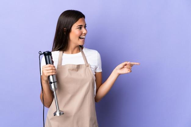 Brazylijska kobieta za pomocą ręcznego blendera na fioletowej ścianie wskazując palcem w bok i przedstawia produkt