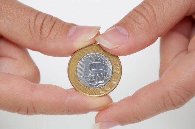 Brazylijska moneta 1 real w kobiecej dłoni