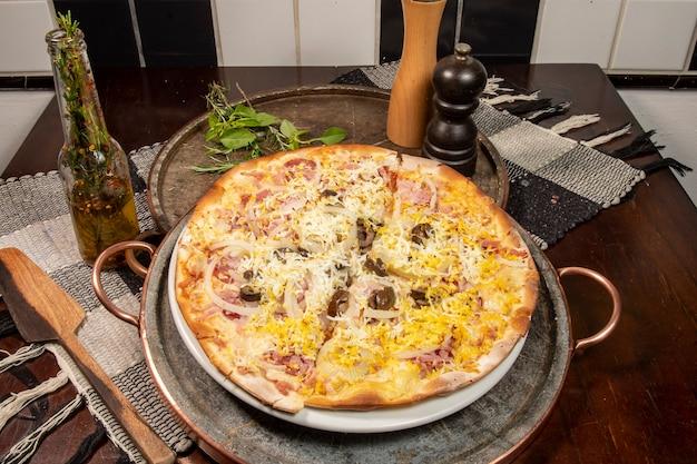 Brazylijska pizza po portugalsku z szynką, jajkiem, papryką, cebulą, mozzarellą, widok z góry