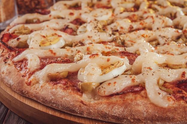 Brazylijska pizza z mozzarellą, kiełbasą calabrese, jajkami, catupiry, oliwą i oregano (pizza especial de calabresa) - zbliżenie.