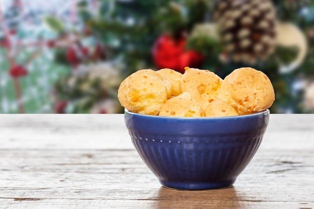 Brazylijska przekąska, chleb serowy, brazylijska przekąska. na świątecznym tle, w niebieskiej ceramicznej puszce.