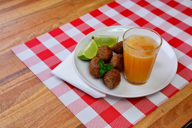 Brazylijska przekąska kibe smażona na głębokim tłuszczu z sokiem pomarańczowym i napojem gazowanym - popularna na lokalnych przyjęciach.