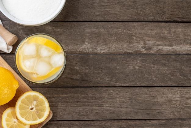 Brazylijska sycylijska caipirinha cytrynowa w szklance z lodem z kawałkami owoców na drewnianej desce z miejscem na kopię