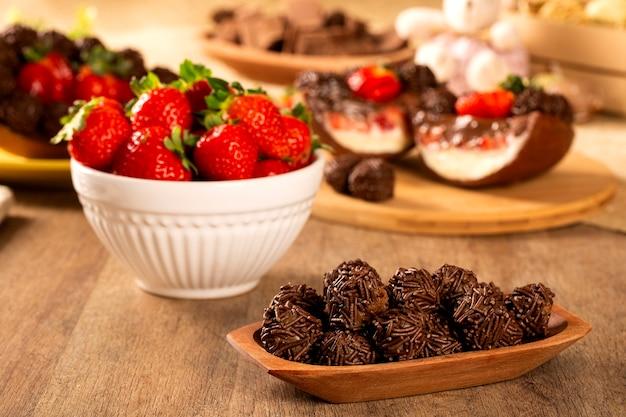Brazylijska trufla czekoladowa bonbon brigadeiro na drewnianym stole z truskawkowym i wielkanocnym tłem.