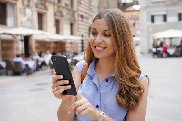 Brazylijska uśmiechnięta kobieta pisząca na telefonie na zewnątrz