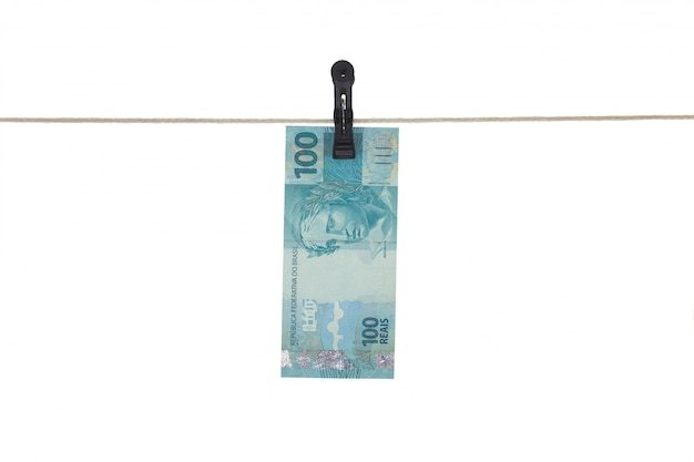Brazylijski 100 istny banknot w clothesline brudnym pieniądze pojęciu - odizolowywającym - pranie brudnych pieniędzy -